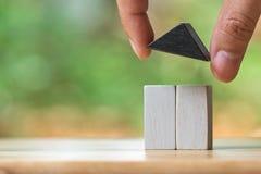 O homem de negócios que guarda um modelo modelo da casa é colocado em uma pilha das moedas utilização como o conceito do negócio  Fotografia de Stock Royalty Free