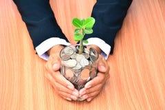O homem de negócios que guardam o vidro e as moedas completas preenchem o vidro e o verde Imagens de Stock Royalty Free