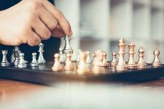 O homem de negócios que joga o jogo de xadrez bateu o oponente com conce da estratégia fotografia de stock