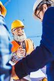 O homem de negócios que olha a construção planeia quando um trabalhador da construção mostrar imagens de stock