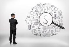 O homem de negócios que olha o negócio rabisca com uma lente de aumento e da vista do sinal de dólar imagens de stock royalty free