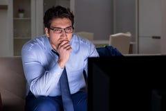 O homem de negócios que olha a tevê na noite tarde foto de stock