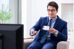O homem de negócios que olha a tevê no escritório fotos de stock royalty free