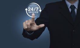 O homem de negócios que pressiona o botão 24 horas presta serviços de manutenção ao ícone no backgr azul Foto de Stock