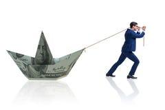 O homem de negócios que puxa o barco feito da cédula do dólar Fotografia de Stock