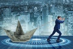 O homem de negócios que puxa o barco feito da cédula do dólar Imagem de Stock Royalty Free