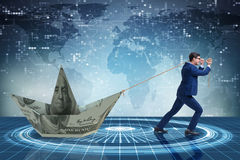 O homem de negócios que puxa o barco feito da cédula do dólar Imagem de Stock