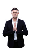 O homem de negócios que reza com suas mãos ajustou-se reza dentro Imagens de Stock