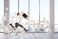 O homem de negócios que salta em uma entrada do escritório, papéis Imagens de Stock Royalty Free
