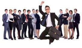 O homem de negócios que salta na frente de sua equipe imagens de stock
