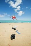 O homem de negócios que salta na praia Fotografia de Stock Royalty Free