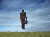 O homem de negócios que salta no campo Fotografia de Stock Royalty Free