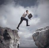 O homem de negócios que salta sobre as montanhas imagem de stock