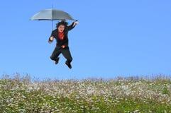 O homem de negócios que salta sobre o monte da grama fotografia de stock