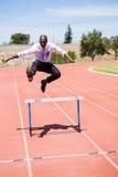 O homem de negócios que salta um obstáculo ao correr foto de stock royalty free