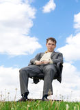 O homem de negócios que senta-se em uma cadeira imagem de stock royalty free