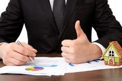 O homem de negócios que senta-se na tabela com casa e assina um contrato Fotografia de Stock Royalty Free