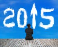 O homem de negócios que senta-se no assoalho de madeira com sinal 2015 da seta nubla-se Imagens de Stock Royalty Free