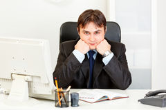 O homem de negócios que sentam-se na mesa e o sustento dirigem nas mãos fotos de stock