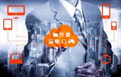 O homem de negócios que toca em uma nuvem conectou a muitos objetos em uma tela virtual, conceito sobre o Internet das coisas Fotos de Stock Royalty Free