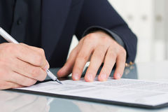 O homem de negócios que trabalha com originais assina acima o contrato Imagem de Stock Royalty Free