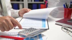 O homem de negócios que trabalha e que calcula, lê e escreve relatórios Empregado de escritório, close up da tabela Conce da cont filme