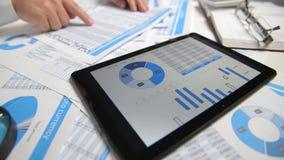 O homem de negócios que trabalha e que calcula, lê e escreve relatórios Usando o PC da tabuleta Empregado de escritório, close up vídeos de arquivo