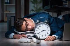 O homem de negócios que trabalha fora do tempo estipulado o muito tempo tarde no escritório foto de stock
