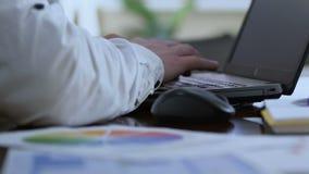 O homem de negócios que trabalha no portátil, preparando a apresentação com estatísticas diagrams vídeos de arquivo