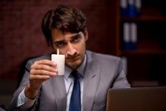 O homem de negócios que trabalha tarde no escritório com luz da vela imagens de stock