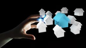 O homem de negócios que usa 3D rendeu casas brancas e azuis pequenas Fotografia de Stock