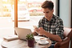 O homem de negócios que usa a escrita do smartphone e do portátil na tabuleta corteja sobre Fotos de Stock
