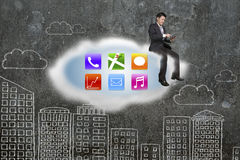 O homem de negócios que usa a tabuleta em ícones do app nubla-se com parede das garatujas Fotografia de Stock Royalty Free