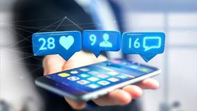 O homem de negócios que usa um smartphone com a gosta, seguidor e messag Fotos de Stock Royalty Free