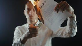 O homem de negócios queima um original do contrato Destruição das seguranças Interrupção de um acordo vídeos de arquivo