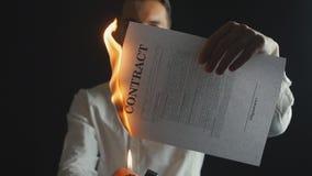 O homem de negócios queima um original do contrato Destruição das seguranças Interrupção de um acordo video estoque