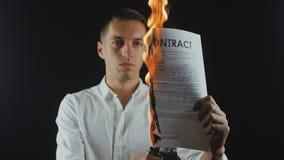 O homem de negócios queima um original do contrato Destruição das seguranças Interrupção de um acordo filme