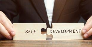 O homem de negócios recolhe enigmas com o Auto-desenvolvimento da palavra Conceito de habilidades e da motivação novas do negócio imagem de stock