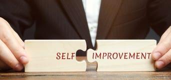 O homem de negócios recolhe enigmas com a Auto-melhoria da palavra Conceito de habilidades e da motivação novas do negócio Pessoa imagens de stock