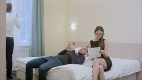 O homem de negócios de relaxamento em uma sala de hotel convida o secretário a fazer edita nos originais Imagem de Stock Royalty Free