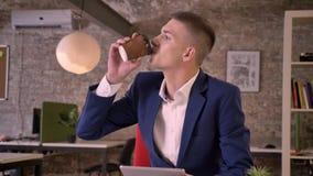 O homem de negócios sério novo está olhando na tabuleta, café da bebida, conceito de uma comunicação, conceito do negócio vídeos de arquivo