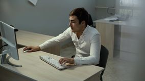 O homem de neg?cios s?rio trabalha no desktop Comerciante que olha o estoque da tela em linha filme
