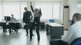 O homem de negócios salta no escritório e dança na frente dos colegas no trabalho O louro severo executa uma dança ritual para vídeos de arquivo