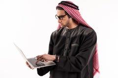 O homem de negócios seguro árabe no keffiyeh está datilografando imagem de stock royalty free