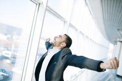 O homem de negócios seguro aprecia seu sucesso que aumenta seus mãos e punhos acima Foto de Stock Royalty Free