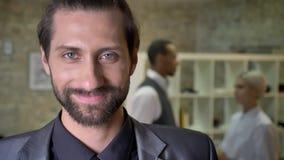 O homem de negócios seguro considerável com barba está olhando na câmera no escritório, sorrindo, colegas está falando no fundo filme
