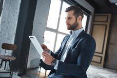 O homem de negócios seguro e novo duro de trabalho no terno à moda está usando sua tabuleta para o trabalho fotos de stock royalty free