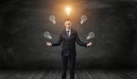 O homem de negócios seguro manipula bulbos com o um que incandesce sobre sua cabeça em um fundo preto Fotos de Stock Royalty Free