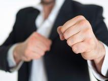 O homem de negócios seguro, suportes com seus punhos em um encaixotamento submete contra uma parede branca Close-up dos punhos Fotos de Stock Royalty Free