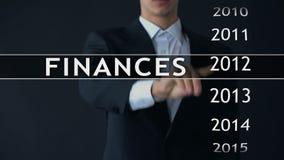 O homem de negócios seleciona um relatório na tela virtual, estatísticas de 2014 finanças do dinheiro vídeos de arquivo